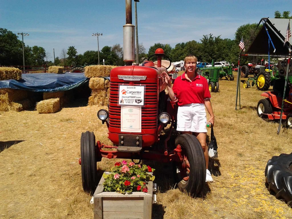 Connie with Noel Brumm's 1947 International ID 6 tractor we sponsor at the Antique Tractor display!